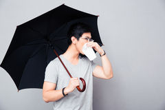 Sick asian man holding umbrella and blowing nose Royalty Free Stock Photo