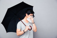 Sick asian man holding umbrella and blowing nose. Over gray background Stock Photo