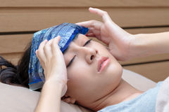 Sick Asian woman caught cold and fever or headache and lying. On bed at home Stock Image