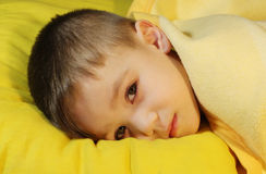 Sick baby. Sick boy 3 years old is lying on yellow pillow Royalty Free Stock Image