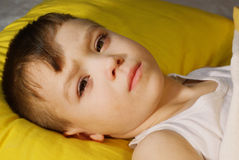 Sick baby. Sick boy 3 years old is lying on yellow pillow Stock Photography