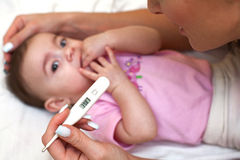 Sick baby being checked for illness. Sick baby being checked for illness and fever Royalty Free Stock Photography