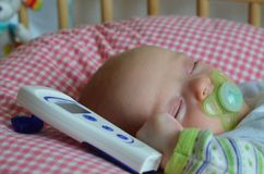 Sick baby is having a rest in the cot. Two months old baby has a fever. He recovers in a cot lying on the pillow. There is a thermometer next to him Stock Photo