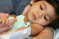 Sick baby in hospital. Looking at IV attatched to arm Royalty Free Stock Images