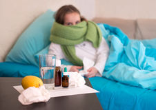 A sick baby lying in bed in front of her face drugs. Girl child with a cold lying in bed shook neck scarf Royalty Free Stock Photography