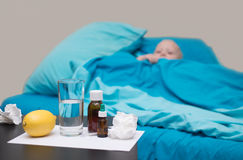 A sick baby lying in bed and looking at thermometer. A sick baby lying in the crib with blue bedding  and looking at thermometer Royalty Free Stock Photography