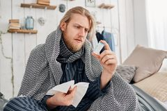 Sick bearded fair-haired man in sleepwear sits on bed surrounded by blanket and pillows, frowns while reading. Sick bearded fair-haired young man in sleepwear Royalty Free Stock Image