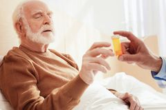 Sick bearded man lying in his bed. Something interesting. Attentive grey-haired male opening mouth and raising hand while taking bow with pills Stock Photo