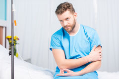 Sick bearded man sitting on hospital bed Royalty Free Stock Photos