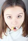 Sick beautiful girl  her mouth full of drugs Royalty Free Stock Image
