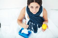 Sick beautiful woman resting in bed at home Royalty Free Stock Images