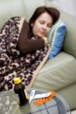 Sick in bed. A woman in bed at home, some medicines on a table. The woman is defocused, the medicines are focused stock images