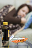 Sick in bed. A woman in bed at home, some medicines on a table. The woman is defocused, the medicines are focused Stock Photos