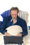Sick in bed with laptop. Royalty Free Stock Photography