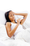 Sick bed woman. Ill woman taking her temperatur in bed wile feeling sick and with fever Stock Photography