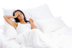 Sick bed woman. Ill woman taking her temperatur in bed wile feeling sick and with fever Stock Photos