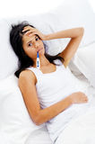Sick bed woman. Ill woman taking her temperatur in bed wile feeling sick and with fever Royalty Free Stock Images