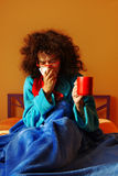 Sick in bed. Woman sitting under a blue blanket in her bed, she is holding a cup and blowing her nose Stock Images