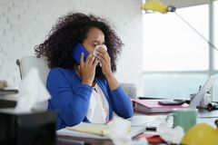 Sick Black Woman Working from Home Sneezing For Cold. Sick african american girl working from home office. Ill young black woman with cold, talking on mobile royalty free stock photos