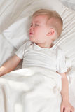 A sick blond toddler wearing white t-shirt lying Royalty Free Stock Photo
