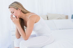 Sick blonde blowing her nose on tissue. At home in the bedroom Stock Images
