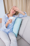 Sick blonde sitting on couch holding tissue Royalty Free Stock Photography