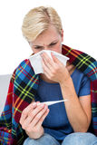 Sick blonde woman blowing her nose and checking the thermometer Stock Photo