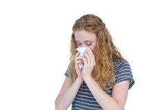 Sick blonde woman blowing her nose Stock Photography
