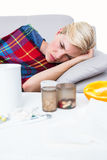 Sick blonde woman lying on the couch Stock Photography