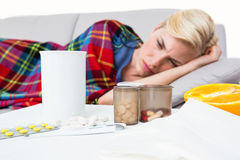 Sick blonde woman lying on the couch Royalty Free Stock Image