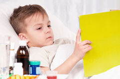 Sick boy. Sick little beautiful boy with book in the bed Stock Images