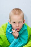 Sick boy. A sick little boy is measuring the temperature Royalty Free Stock Photography