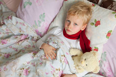Sick boy is in bed. Sick boy is laying in bed with his teddy bear. Them temperature are measured thermometer Stock Images