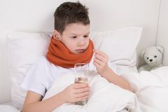 Sick boy in bed, drinks medicine pill, washing down with water stock image