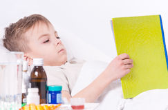 Sick boy in bed reading book Stock Image