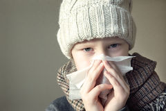 Sick boy blowing his nose Royalty Free Stock Photos