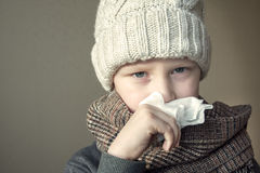 Sick boy blowing his nose Royalty Free Stock Photo