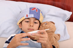 Sick boy consulting thermometer Stock Photo