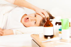 Sick boy crying while mother checking temperature. Sick five years old boy laying in bed and crying while mother checking temperature stock photo