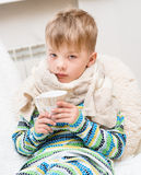 Sick boy with a cup in his hand sitting on the bed Royalty Free Stock Images