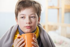 Sick boy with a cup of tea at home.  stock photography