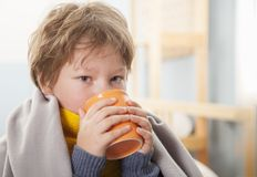 Sick boy with a cup of tea at home royalty free stock image