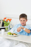 Sick boy having food in hospital bed Royalty Free Stock Photography