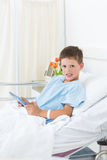 Sick boy holding digital tablet in hospital Stock Photography