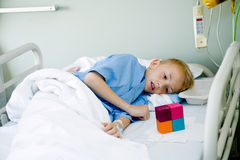 Sick boy in hospital bed with his toy Royalty Free Stock Photos