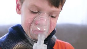 Sick boy inhaling through inhaler mask. Use nebulizer and inhaler for the treatment. Sick boy inhaling through inhaler mask. Use nebulizer and inhaler for the stock video footage