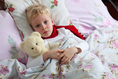 Sick boy lies in bed Stock Photo