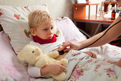 Sick boy lies in bed Stock Photography