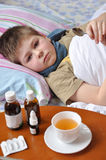 Sick boy lying in bed. Stock Photo
