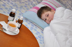 Sick boy lying in bed. Stock Images